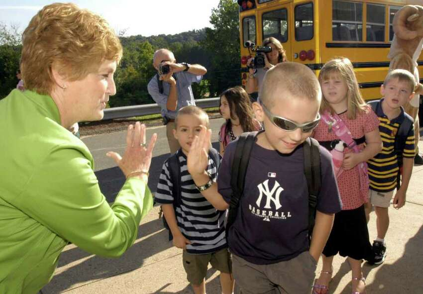 Governor M. Jodi Rell high-fives a fellow Yankees fan , Ben Webb, as he arrives at school for his first day of 5th grade. Gov. Rell was at Rockwell Elementary School Tuesday greeting children on the first day of school.
