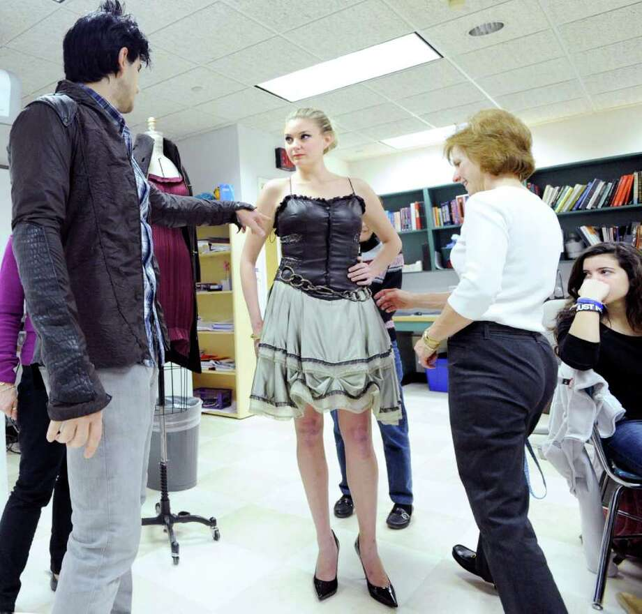 "Greenwich fashion designer Jason Troisi, left,  who was on the last season of the popular reality show ""Project Runway,"" shows off one of his dresses on model Anna McGhee as Greenwich High School teacher, Sherry Myer, right, inspects the design during a visit by Troisi to a Greenwich High School fashion design class, Friday morning, Dec. 17, 2010. Photo: Bob Luckey / Greenwich Time"