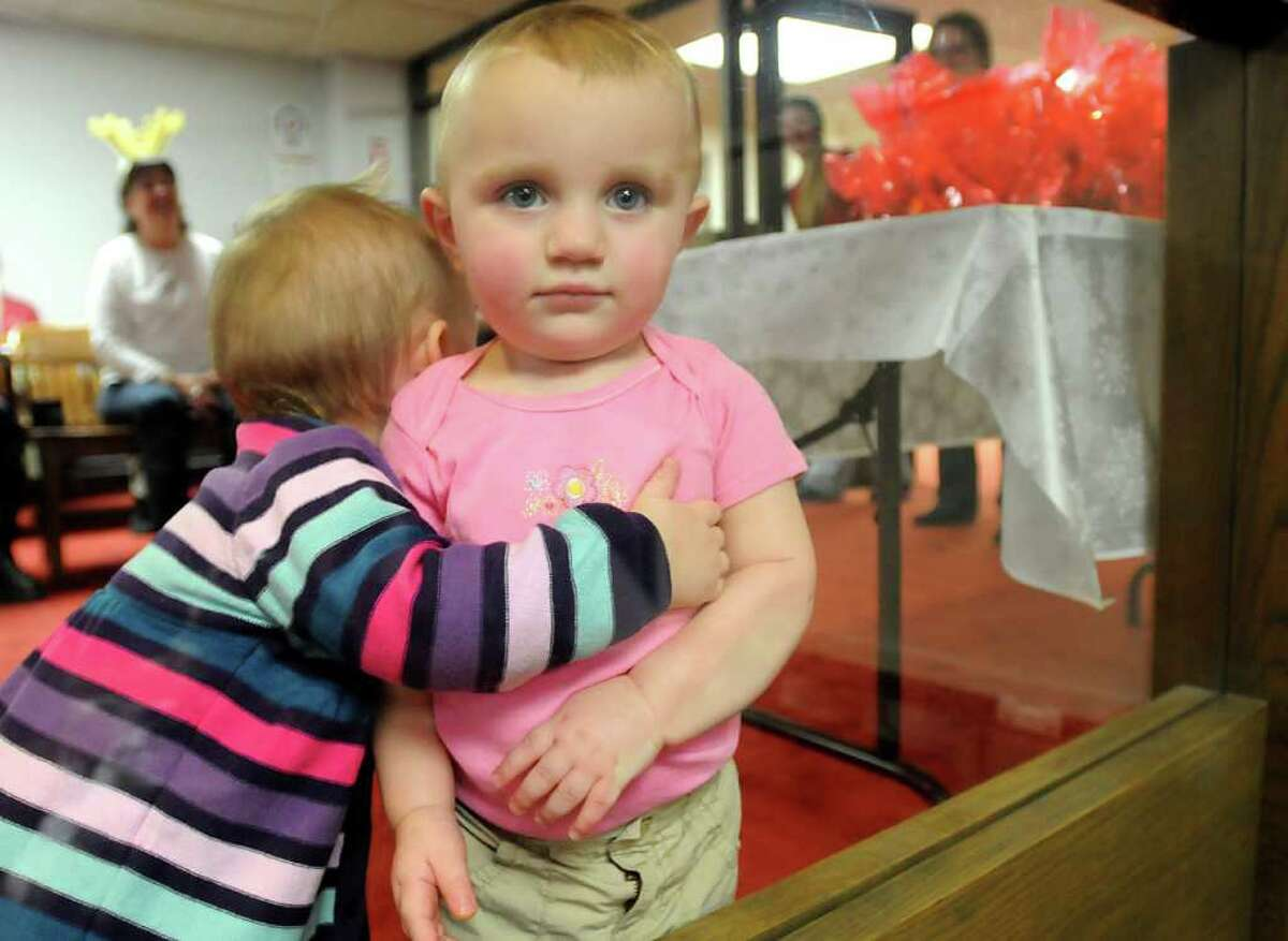 Camilla Desso, left, 17 months, of North Greenbush hugs Gianna Marra, 18 months, of Schodack during the Vanderheyden Christmas party at the chambers of the Rensselaer County Legislature in Troy, NY, on December 17, 2010. (Lori Van Buren / Times Union)