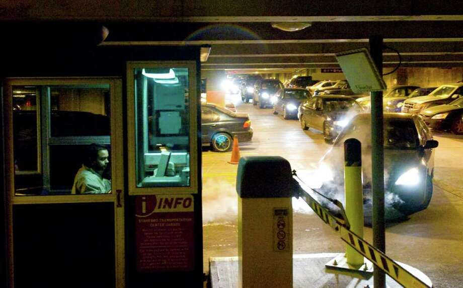 FILE — A long line of cars waits to pay an attendant before leaving the garage at the Stamford rail garage on Station Place in Stamford, Conn. Photo: Keelin Daly / Stamford Advocate