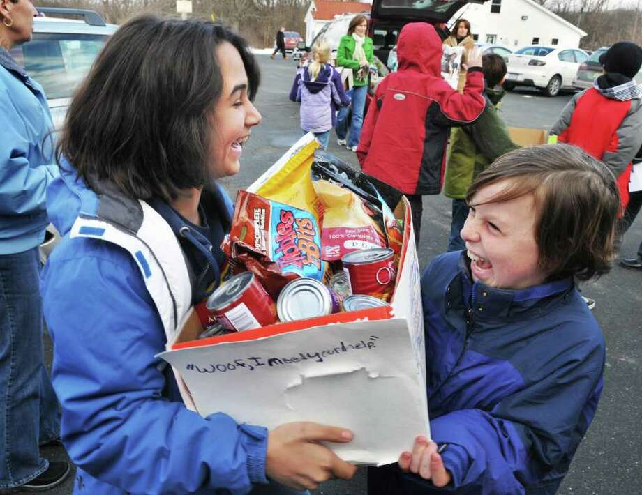 Tahlia Maldanada, 11, and David Hamlin, 9, students at Susan Odell Taylor School in Troy, deliver collected items from the Humane Society's Wish List on Friday during a class tour of the Mohawk and Hudson River Humane Society in Menands.  (John Carl D'Annibale / Times Union) Photo: John Carl D'Annibale / 00011421A