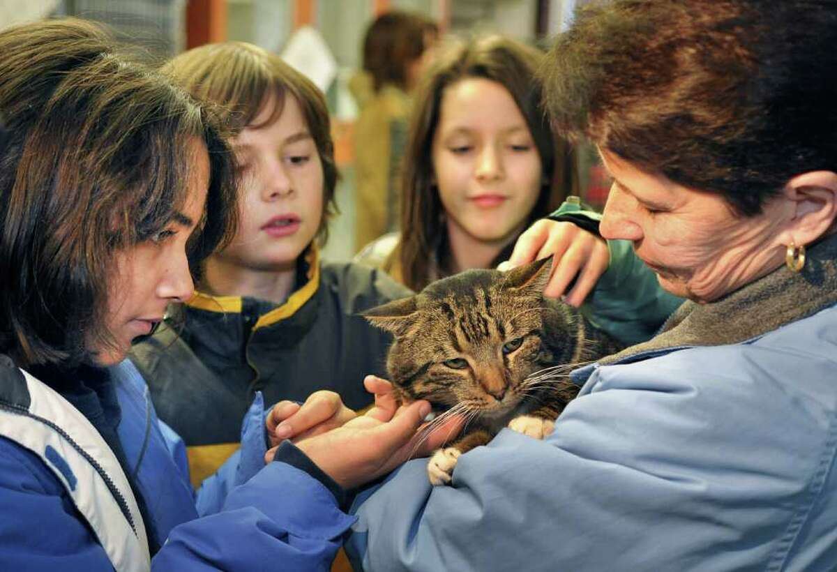 Students from Susan Odell Taylor School in Troy, from left, Tahlia Maldanada, 11; Trey Briccetti, 10; and Heather Moss,10, pet Barnie with their teacher and animal shelter volunteer Barb McNamee during a class tour on Friday of the Mohawk and Hudson River Humane Society in Menands. (John Carl D'Annibale / Times Union)