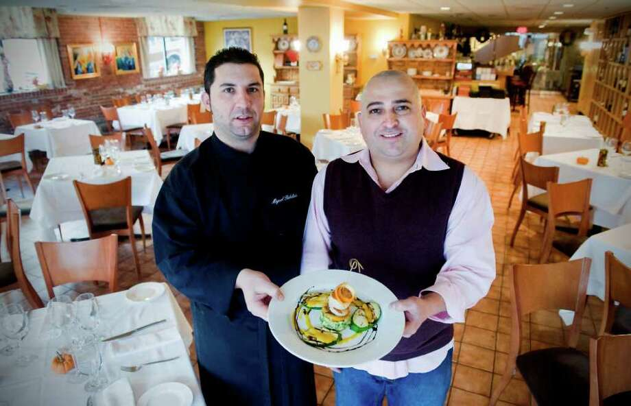 Carlos Hernandez, owner and chef of Miegas Restaurant, and Miguel Angel Rebolledo, executive chef, in the dining room of Miegas with the grilled sea scallops and avocado salad in Norwalk, Conn on Thursday December 16, 2010. Photo: Kathleen O'Rourke / Stamford Advocate