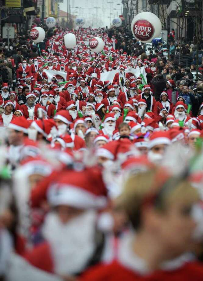 People dressed as Santa Claus participate in the annual Santa Claus parade, Sunday Dec. 12 2010 in Porto, Portugal. Thousands staged a parade in an attempt to break the Guinness Book of records of most people dressed as Santa Claus. (AP Photo/Paulo Duarte)