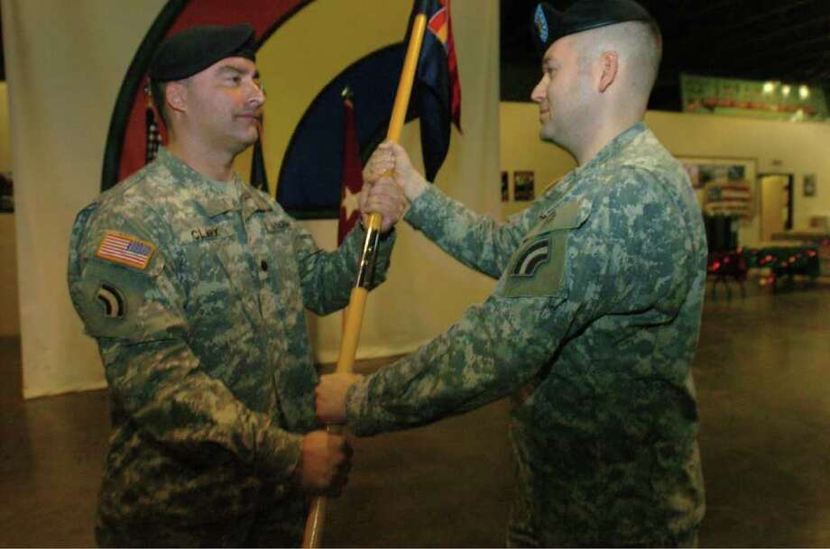 Army National Guard Capt. Todd Balog, right, receives the unit guidon of the 42nd Infantry Division Headquarters Company from Lt. Col. Russell Clark, Special Troops Battalion commander, during a change of ceremony Dec. 11 at the Glenmore Road Armory in Troy. (Photo by Sgt. John Smith / State Department of Military and Naval Affairs)