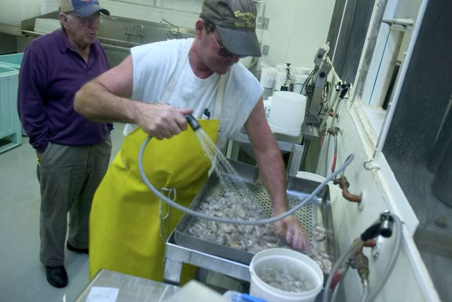 Arnold's Seafood Sales owner Buddy Treybig sifts through oysters during a quality inspection for wholesaler distributor Jimmy Evans. Evans swears by the quality of oysters provided by Treybig. TIMOTHY C. BAKER/SPECIAL TO THE EXPRESS-NEWS