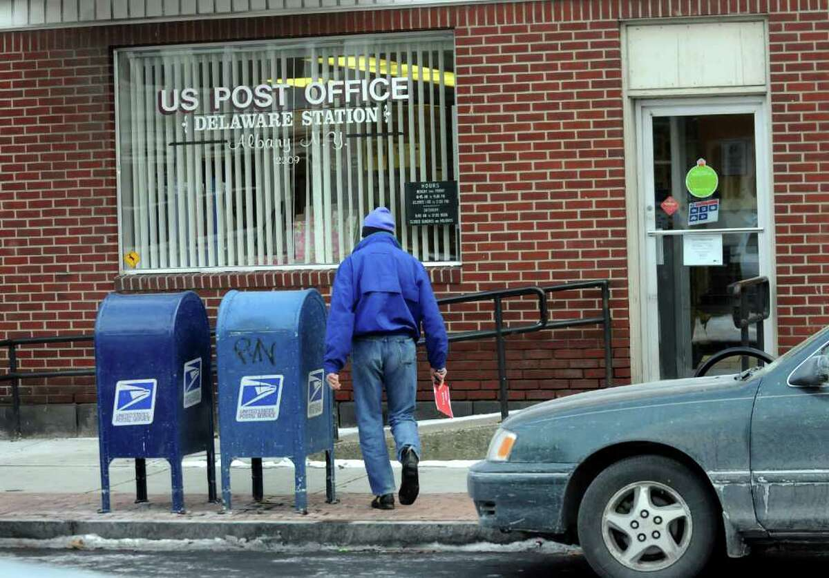 David H. Cohen, who grew up in Albany's Delaware Avenue neighborhood, mails a letter on Dec. 17 at the Delaware Station Post Office. (Cindy Schultz / Times Union)