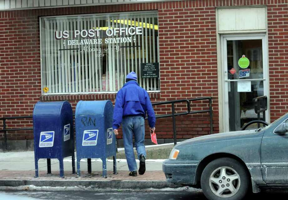 David H. Cohen, who grew up in Albany's Delaware Avenue neighborhood, mails a letter on Dec. 17 at the Delaware Station Post Office.  (Cindy Schultz / Times Union) Photo: Cindy Schultz