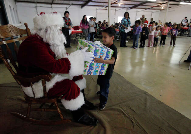 A young boy beams after receiving a gift from Santa Claus (USAA employee Kyle Corley) during a Christmas party thrown by USAA and Joven Inc. at Mount Carmel Catholic Church recently. Joven helps kids ages 4-17 at school and after school. Photo: Kin Man Hui/kmhui@express-news.net