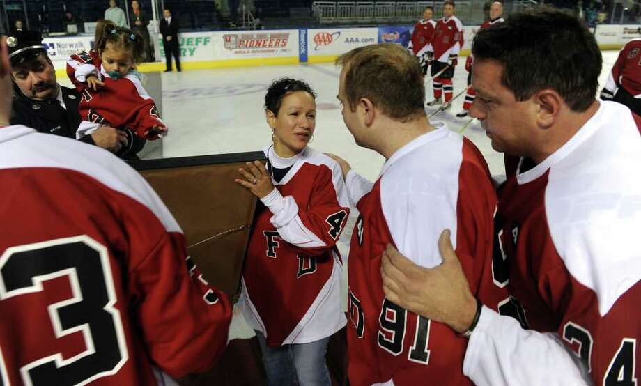 Bridgeport firefighters Jim Buck, center, and Bill Borosky, right, greet Marianne Velasquez in a retirement ceremony for her husband's jersey number, before a charity hockey game between firefighters from the Bridgeport and Worcester, Mass. fire departments was held at the Arena at Harbor Yard in Bridgeport, Conn. on December 18, 2010. The game was held in honor of firefighters Michel Baik and Steven Velasquez, who died fighting a house fire this past July. Velasquez was an active member on the department's hockey team. Proceeds raised from the event go to the Bridgeport Fallen Firefiighters Fund. Photo: Christian Abraham / Connecticut Post