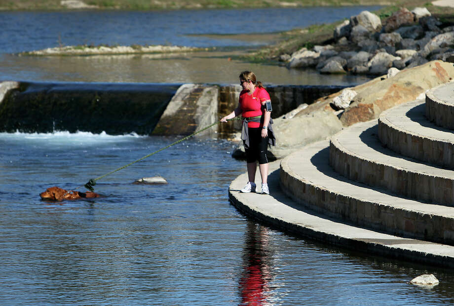 Resident Mary Flannigan holds onto her golden retriever, Sasha, as the canine takes a cool dip in the San Antonio River. County and San Antonio River Authority officials kicked off the soft opening of the Mission Reach of the San Antonio River Project with tours near Roosevelt Park on Saturday. The newly restored section features new hike and bike trails for public use. Photo: Kin Man Hui/kmhui@express-news.net