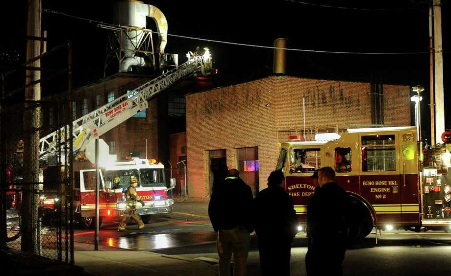 Shelton firefighters put out a small fire an old factory building along Canal Street in downtown Shelton, Conn. on Saturday December 18, 2010. According to fire officials on the scene, a large generator that was placed on the roof of the building caught fire. Photo: Christian Abraham / Connecticut Post