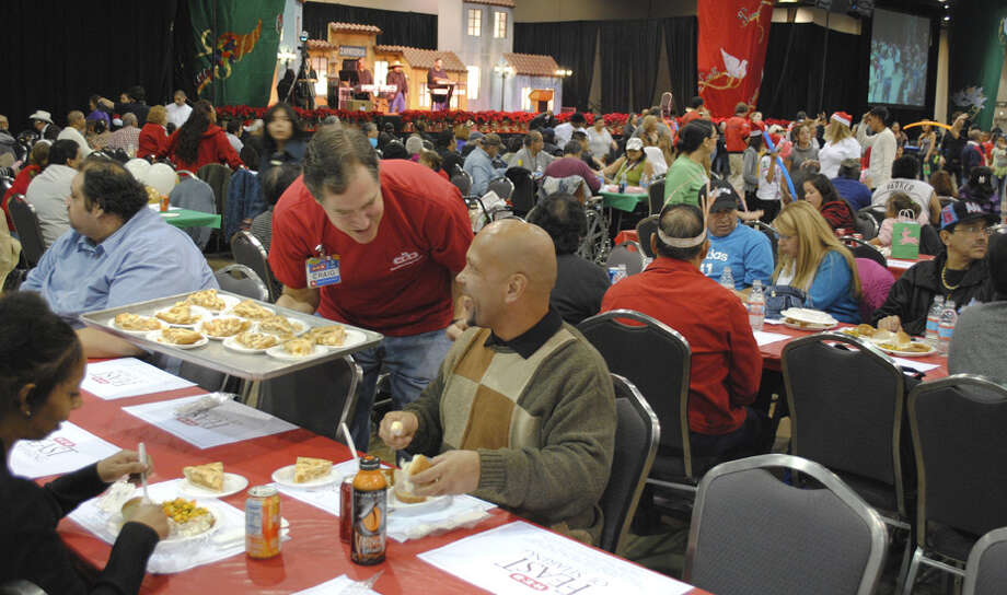 H-E-B President and Chief Operating Officer Craig Boyan, holding a tray of apple pies, talks with a Feast of Sharing guest at the Convention Center. Photo: Courtesy Of H-E-B