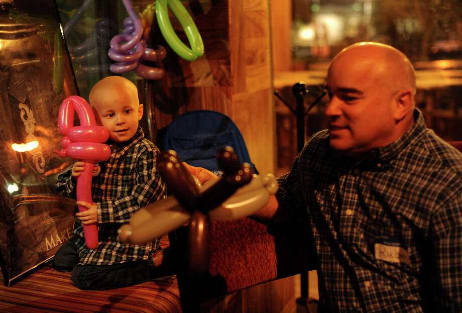 Reid Smith, 3, and his father, Ruben Smith, play with balloons during the Make-A-Wish Foundation of Central and South Texas departure party at Barbaresco restaurant. Reid, who has cancer, is going to Disney World. Photo: BILLY CALZADA/gcalzada@express-news.net / SAN ANTONIO EXPRESS-NEWS