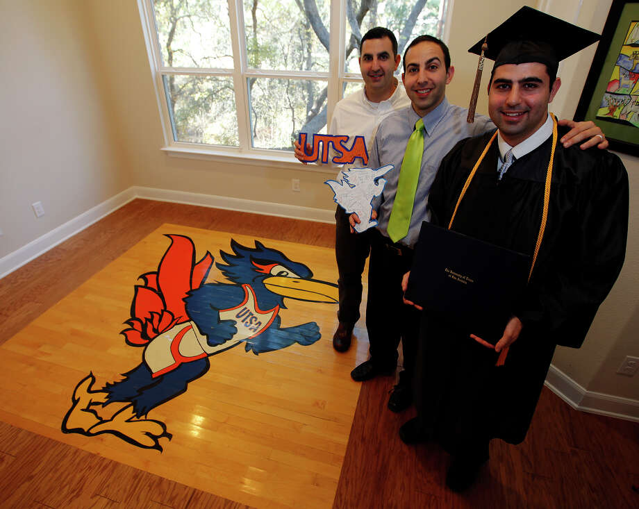Aryeh Kluger is the last of five brothers to graduate from UTSA. With him are brothers Aaron (left) and Jacob, standing by the piece of UTSA basketball court Jacob bought. Photo: Kin Man Hui/kmhui@express-news.net