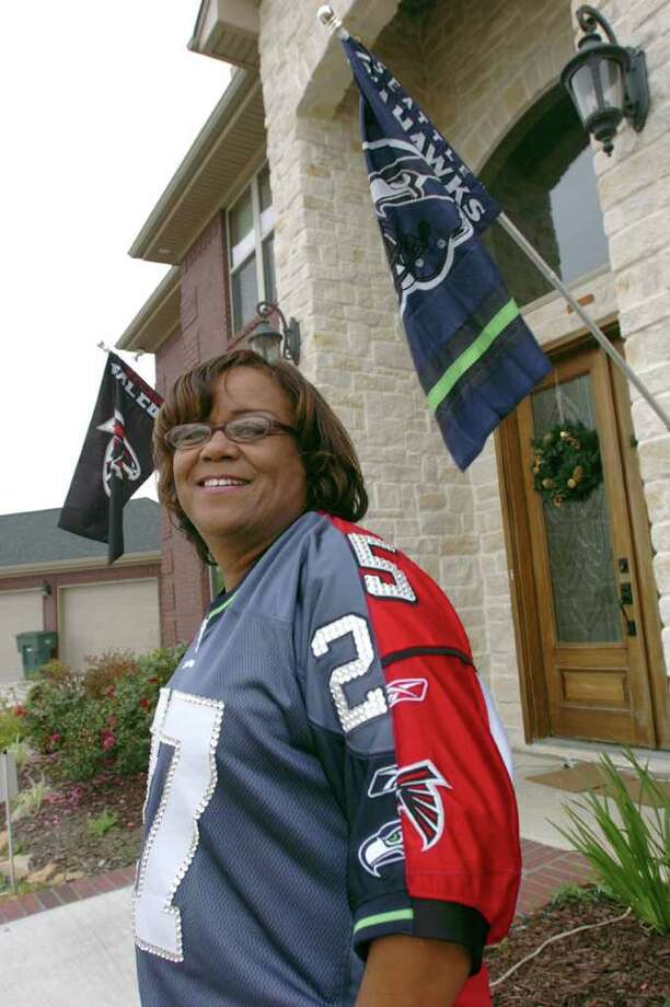 Barbara Babineaux will be in Seattle for Sunday's N.F.L. game between the Atlanta Falcons and the Seattle Seahawks. Babineaux's son Jonathan plays for the Falcons and her sone Jordan plays for the Seahawks, hence her jersey melding the teams colors and logos with Jonathan's number on the fron and Jordan's on the back. Pete Churton/The Enterprise Photo: Pete Churton / Beaumont