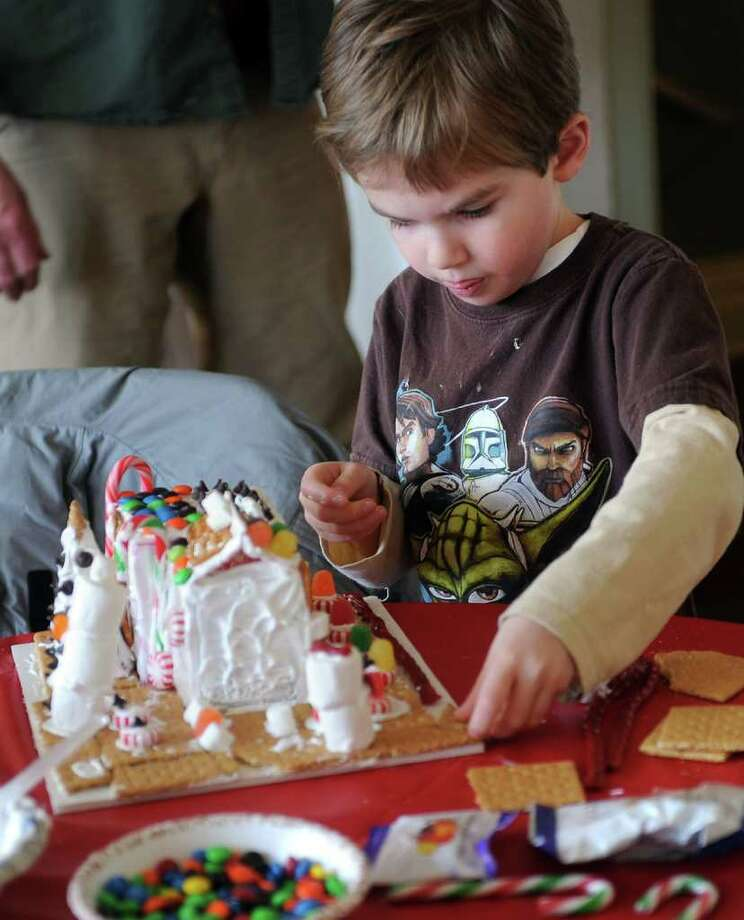 Frank Sadabos, 5, of Fairfield, concentrates on making his candy house as he takes part in Fairfield Museum and History Center's Candy House Workshop which was held at the Burr Homestead in Fairfield, Conn. on December 18, 2010. Adults and children alike created their own houses constructed with graham crackers, icing, gumdrops, licorice, and other sweets. Photo: Christian Abraham / Connecticut Post