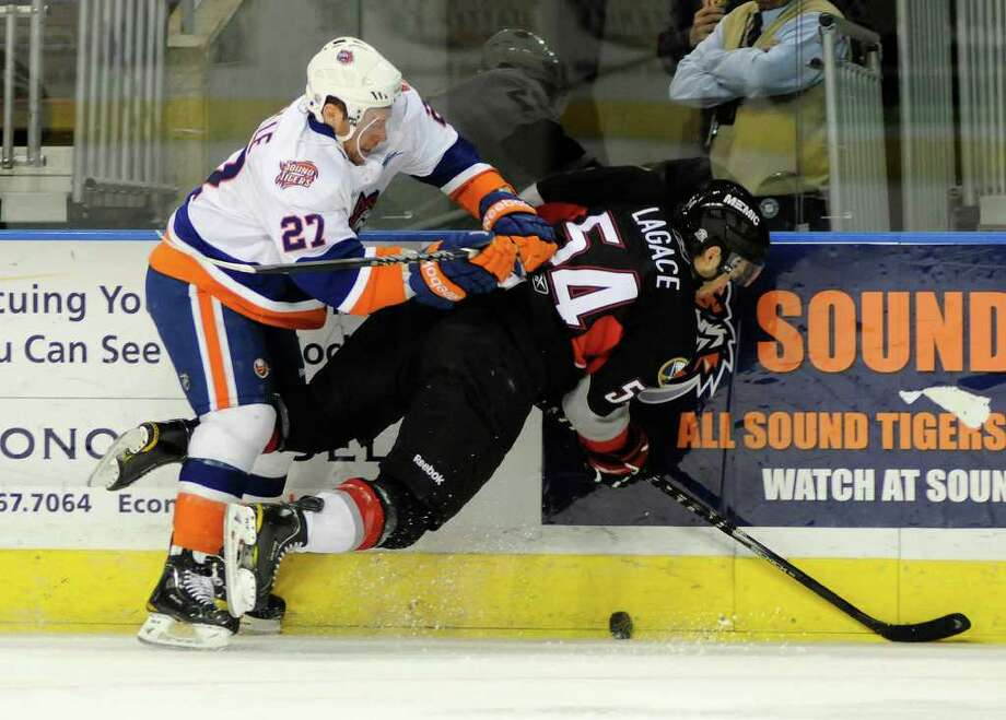 Olivier Labelle (#27) of the Sound TIgers collides with Jacob Lagace (#54) of the Pirates as the Bridgeport Sound Tigers host the Portland Pirates at the Arena at Harbor Yard in Bridgeport, CT on Sunday, December 19, 2010. Photo: Shelley Cryan / Shelley Cryan freelance; Connecticut Post freelance