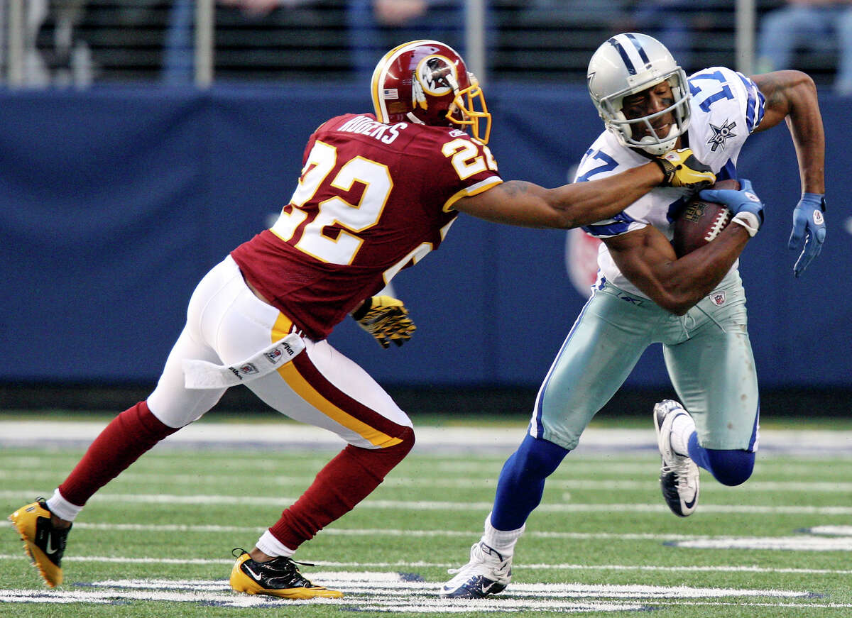 The Dallas Cowboys' Sam Hurd looks for room around the Washington Redskins' Carlos Rogers during the first half on Sunday, Dec. 19, 2010, at Cowboys Stadium in Arlington. The Cowboys won 33-30.