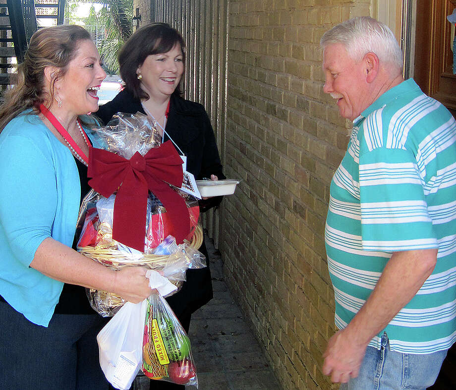 Meals on Wheels volunteers Nancy Compton-Willaford (left) and Meghan Grace deliver a food basket to James Carney. Photo: Courtesy Meals On Wheels