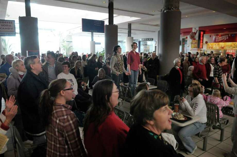Members of a flash mob perform the Hallelujah Chorus in the food court at Crossgates Mall in Guilderland on Sunday, Dec. 19, 2010.  Over 75 singers from choirs around the region took part in the event.  (Paul Buckowski / Times Union) Photo: Paul Buckowski / 00011483B