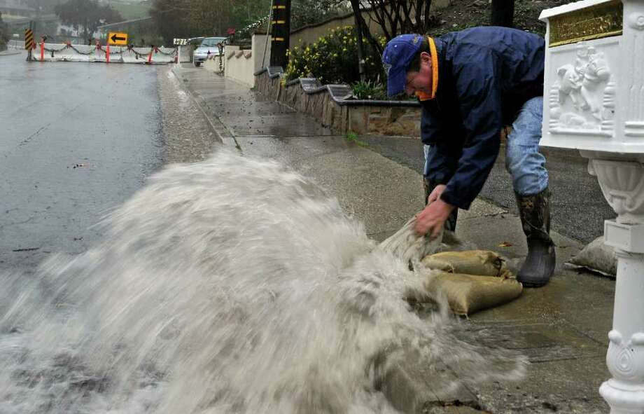 Tom Smith lays sandbags in front of his mailbox to protect it from rushing water in an area that sits below where the 2009 Station Fire occurred and is now in danger of flooding, Sunday, Dec. 19, 2010, in La Canada Flintridge, Calif. (AP Photo/Mark J. Terrill) Photo: Mark J. Terrill