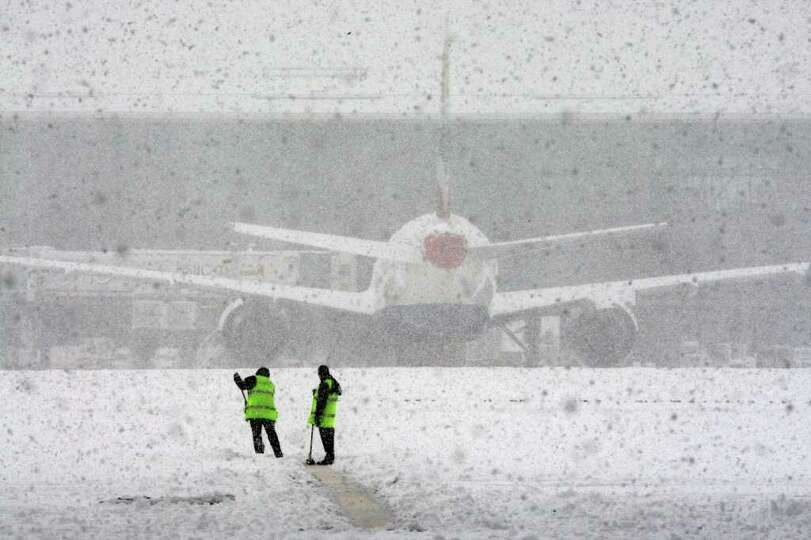 Workers try to clear the snow at London's  Heathrow Airport, after all flights at the airport were g