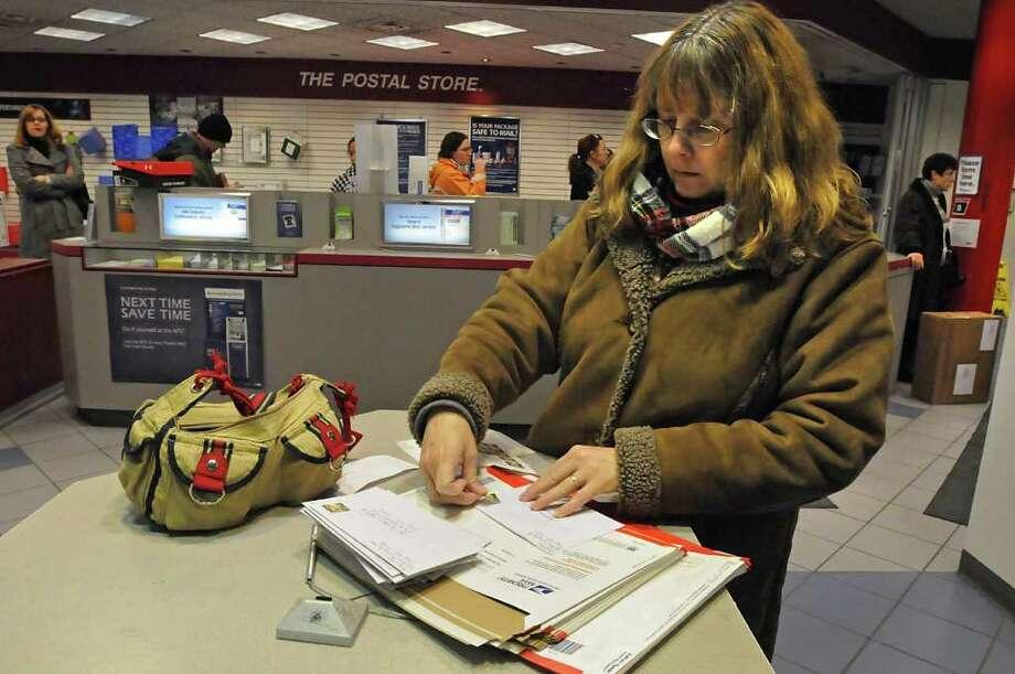 Joelle Augustine of Lansingburgh puts stamps on her holiday cards on the busiest mail day at the U.S. Post Office on Karner Road in Colonie, NY, on December 20, 2010.  (Lori Van Buren / Times Union) Photo: Lori Van Buren