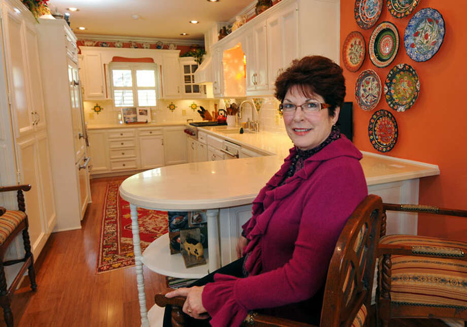 Pam Stewart chose white cabinets accented with architectural details to contrast with the orange walls and bamboo floor in her kitchen. The nine-month project to revamp the kitchen in the 1970 house is in the final tweaking stage.PHOTO BY ROBIN JERSTAD/Special to the Express-News
