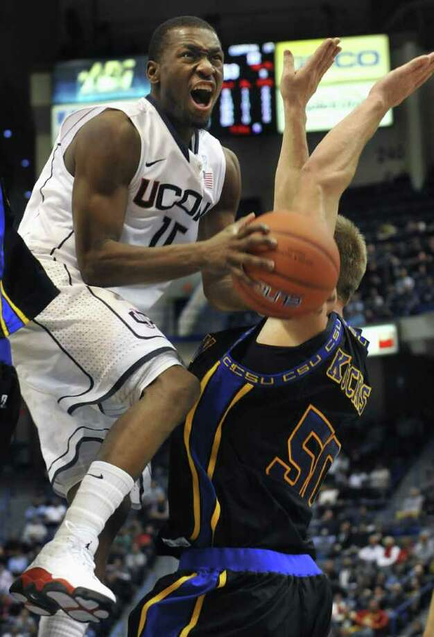 Connecticut's Kemba Walker, left is fouled by Coppin State's Ceslovas Kucinskas during the first half of an NCAA college basketball game in Hartford, Conn., Monday, Dec. 20, 2010. (AP Photo/Jessica Hill) Photo: AP