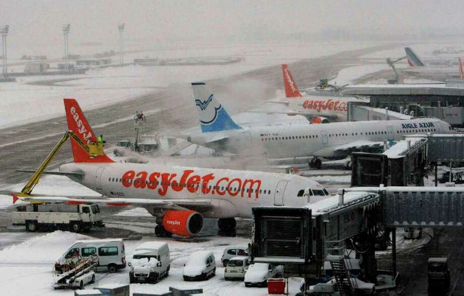 Planes is deiced at at Orly Airport south of Paris Monday, Dec. 20, 2010. Heavy snow on Monday shut down European airport runways; forced fast trains to slow down and left cars skidding through icy; slushy streets on a weekend where many people were trying to head home for the holidays. (AP Photo/Jacques Brinon) Photo: Jacques Brinon / AP
