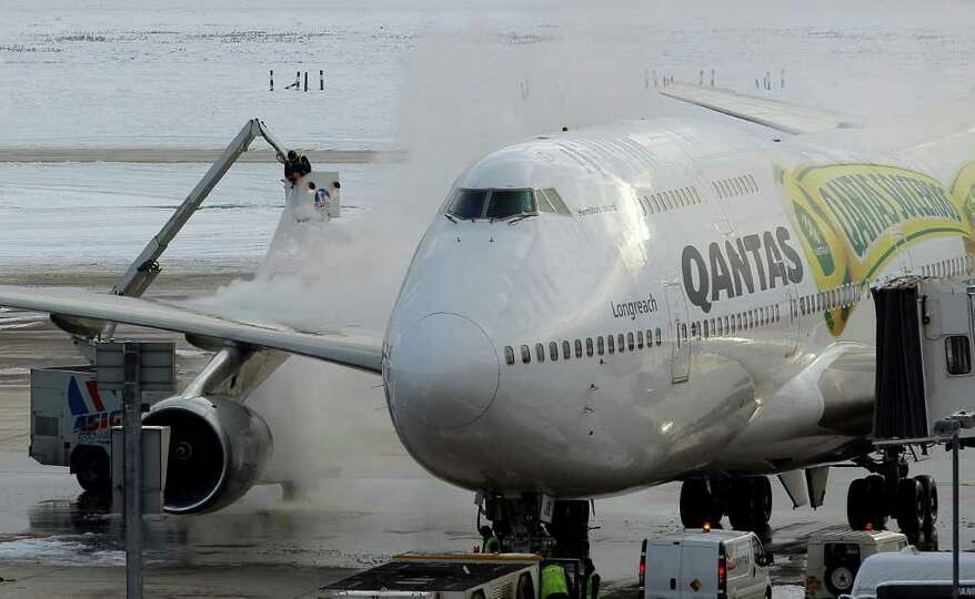 Workers defrost a QANTAS plane at Heathrow Airport in London, Monday, Dec. 20, 2010. Snow and freezi