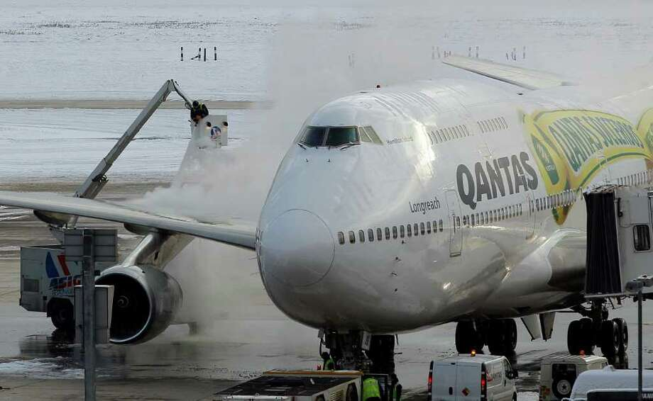 Workers defrost a QANTAS plane at Heathrow Airport in London, Monday, Dec. 20, 2010. Snow and freezing temperatures continued to cause holiday travel chaos for road, rail and air passengers in Britain and much of Europe Monday, raising fears that many will not get home in time for Christmas. (AP Photo/Kirsty Wigglesworth) Photo: Kirsty Wigglesworth / AP
