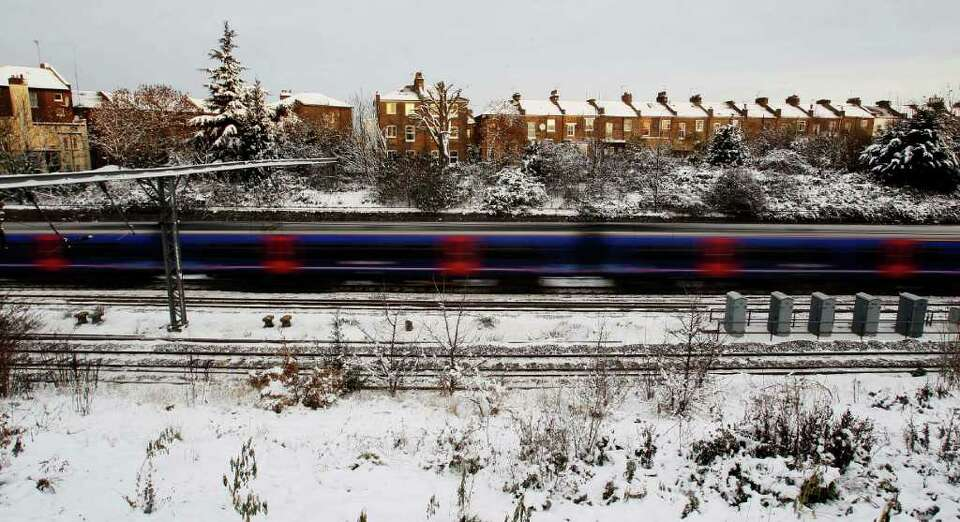 A train drives in Acton, London, Monday, Dec. 20, 2010. British authorities say snow and freezing te