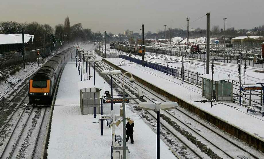 A train drives through a deserted station during the morning peak rush hour in Acton, London, Monday, Dec. 20, 2010. British authorities say snow and freezing temperatures are continuing to cause chaos for road, rail and air passengers after a weekend of disruption. (AP Photo/Kirsty Wigglesworth) Photo: Kirsty Wigglesworth / AP