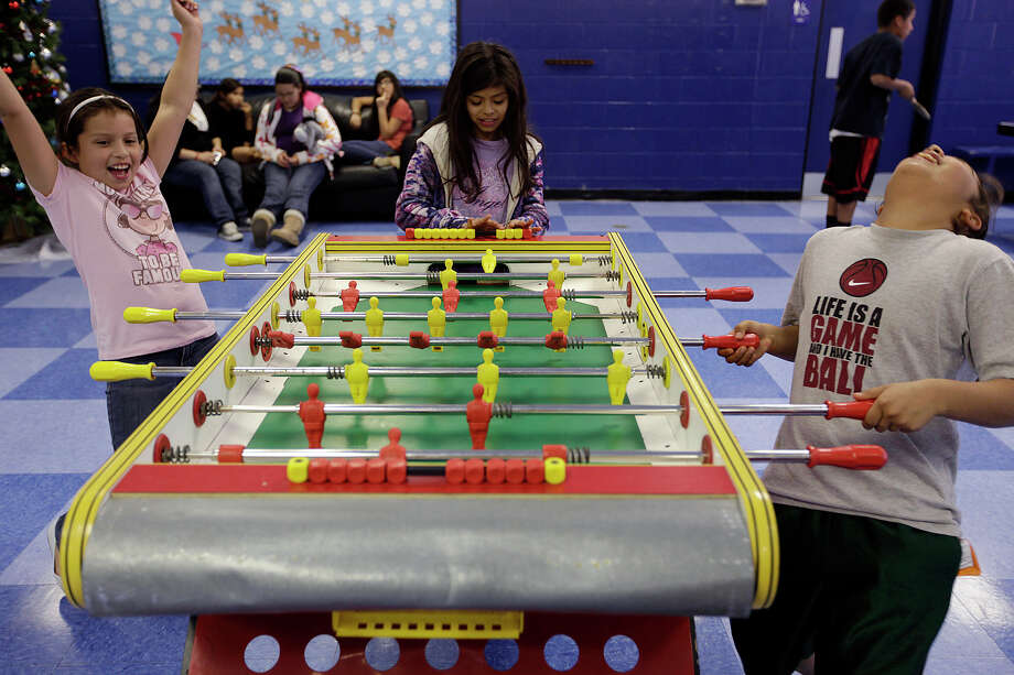 Mercedes Vergara, 10, celebrates a score as she plays table soccer against Gabby Guzman, 10, at the Calderon Boys & Girls Club on the West Side. Watching the game on Monday was Lucy Torres, who also is 10. Photo: Jerry Lara/Express-News