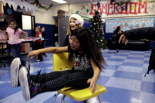 Aliyah Manzano, 9, claims the last chair from Beezle Lopez, 8, during a game of musical chairs at the club on Monday, which was the first day of its holiday schedule. Photo: Jerry Lara/Express-News