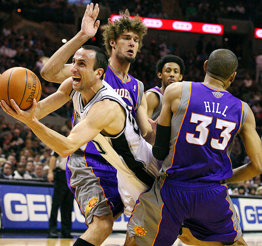 Spurs' Manu Ginobili looks for room between Suns' Robin Lopez and Suns' Grant Hill during first half action Monday Dec. 20, 2010 at the AT&T Center. Ginobili was fouled by Hill on the play. Photo: EDWARD A. ORNELAS/eaornelas@express-news.net