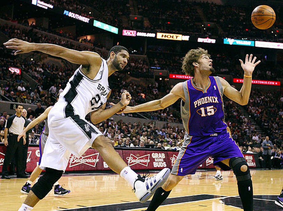 Spurs' Tim Duncan and  Suns' Robin Lopez struggle for a rebound during first half action Monday Dec. 20, 2010 at the AT&T Center. Photo: EDWARD A. ORNELAS/eaornelas@express-news.net