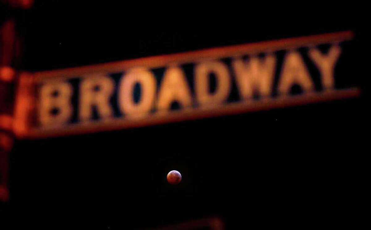 NEW YORK, NY - DECEMBER 21: A Broadway street sign is illuminated while in the distance a total lunar eclipse occurs as the full moon is shadowed by the Earth on December 21, 2010 in New York City. The lunar eclipse was visible during the early morning hours in North and Central America, revealing what seemed to onlookers as an eerie reddish glow on the moon. (Photo by Chris Hondros/Getty Images)