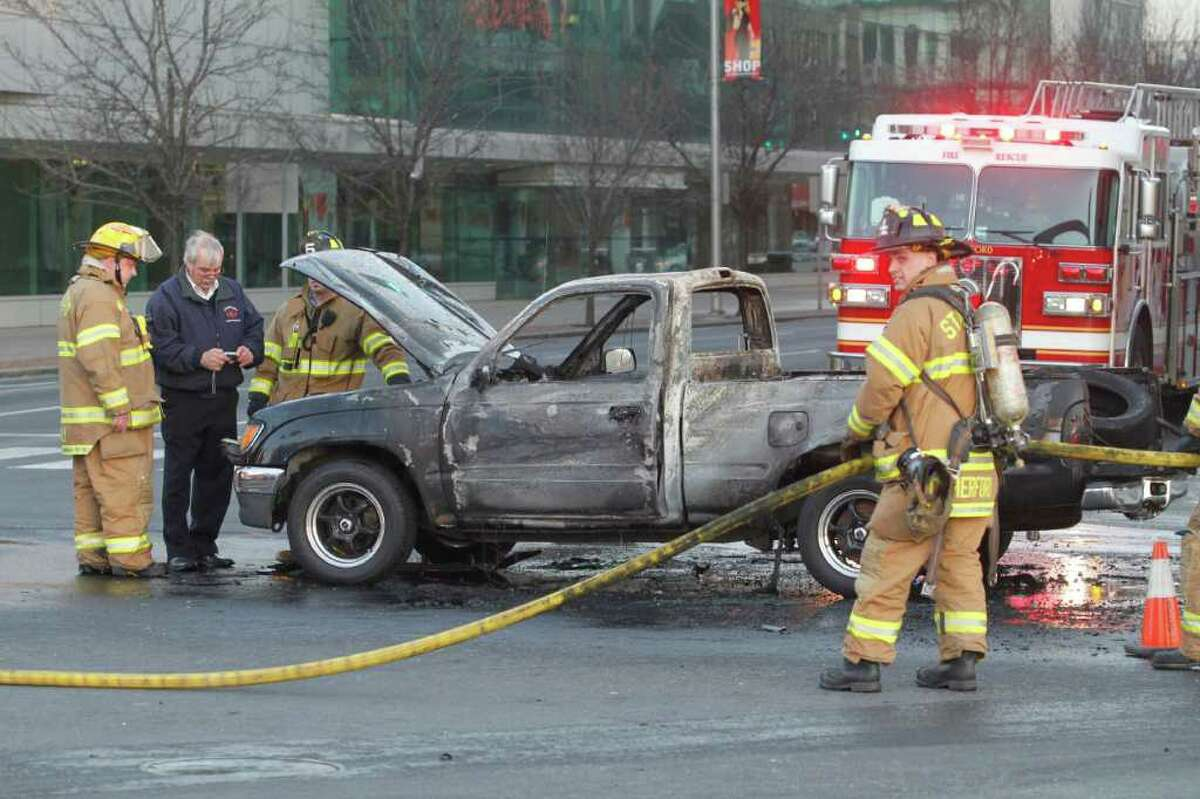 Deputy Fire Marshal Terry Shay, left, and Stamford Fire and Rescue Department firefighters inspect a truck that caught fire at the intersection of Washington Blvd. and Broad St. in Stamford on Monday, Dec. 20, 2010.