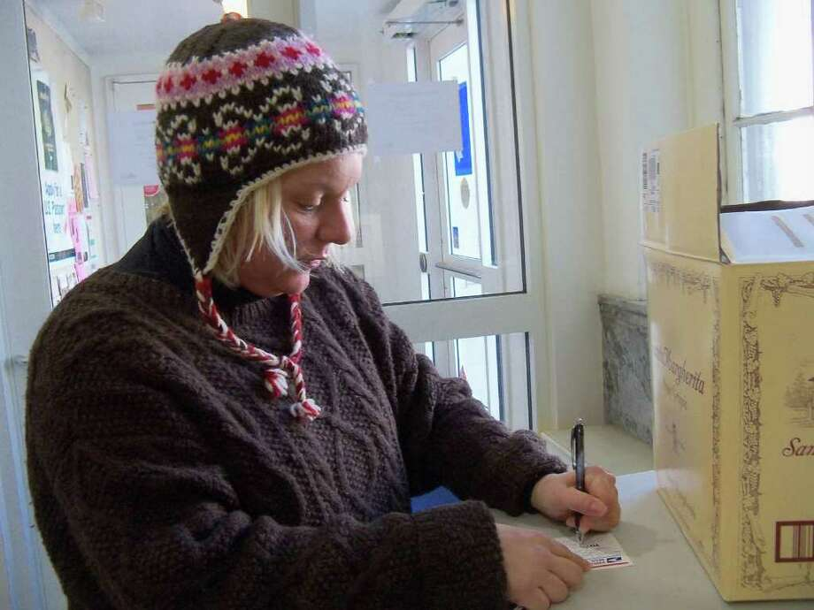 Westport resident Melanie Smith fills out a mailing label in the lobby of the U.S. Post Office on Post Road East Tuesday morning. She's hoping the Christmas gift she bought for her aunt in Tennessee gets there on time. Photo: Genevieve Reilly / Westport News