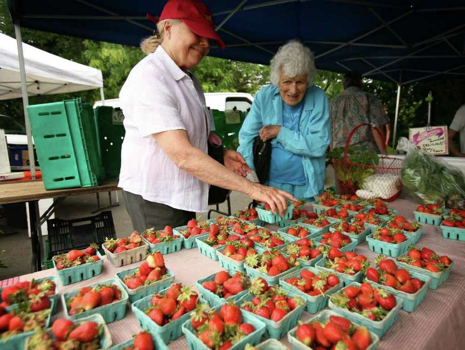 Johanna Gencarella, left of Greenwich, and Peggy Rabut of Westport shop for fresh strawberries on the opening day of the Westport Farmers Market on Thursday, May 27, 2010. Photo: Brian A. Pounds, ST / Connecticut Post