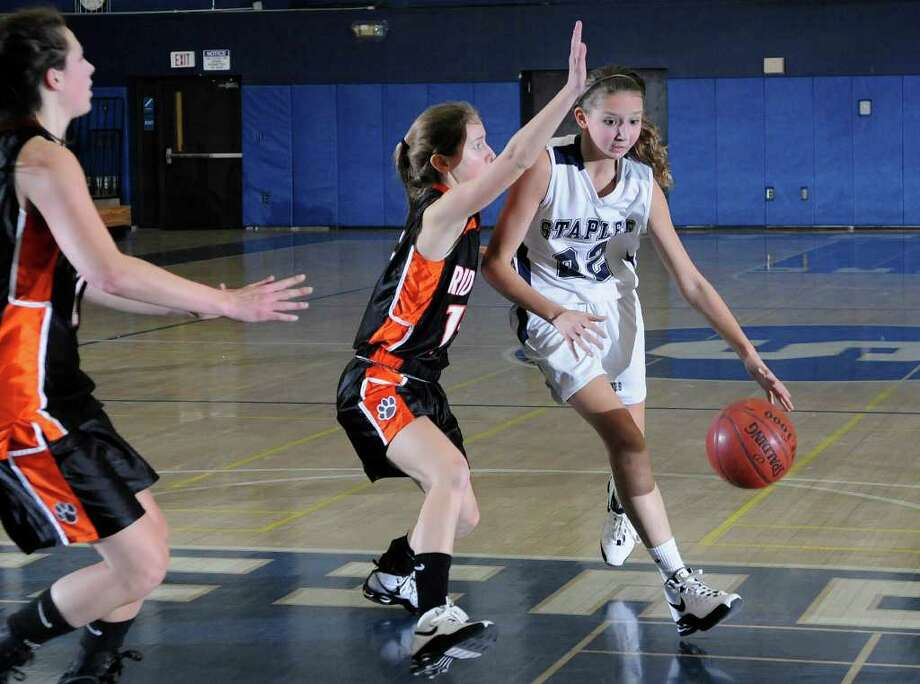 Staples' #22 Nikki Bukovsky dribbles past Ridgefield's #15 Maddie Wiley as Staples High School hosts Ridgefield High School in girls basketball in Westport, CT on Wednesday December 15, 2010. Photo: Shelley Cryan / Shelley Cryan freelance; Connecticut Post freelance