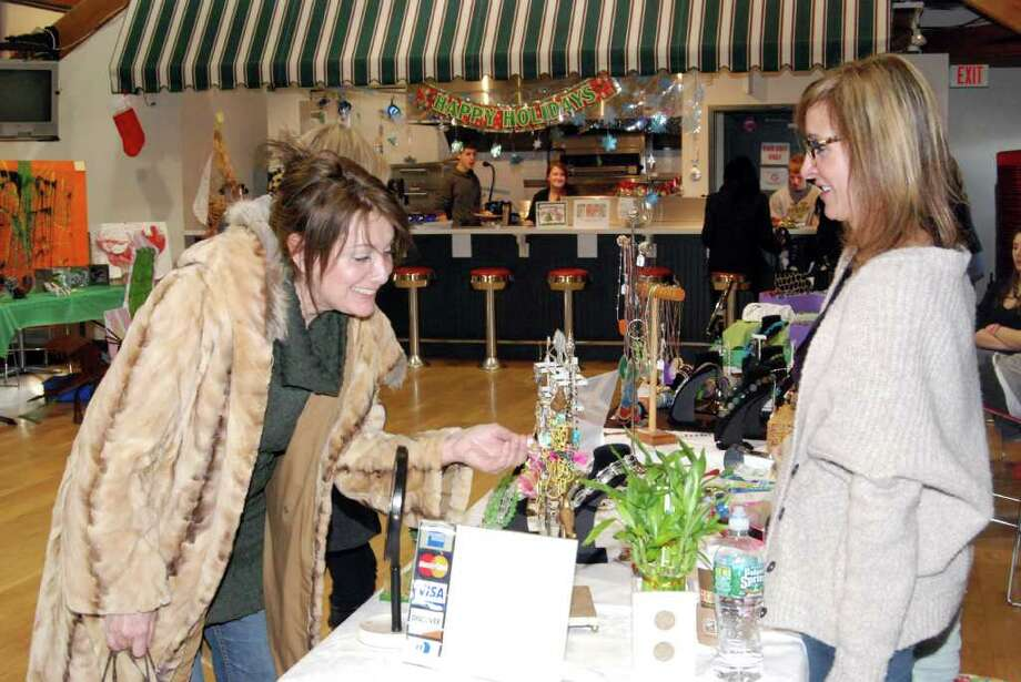Susie Covino is impressed with jewelry designer Victoria Germann's earrings and necklaces at the Outback Artisan's Fair last Saturday. Photo: Jeanna Petersen Shepard / New Canaan News