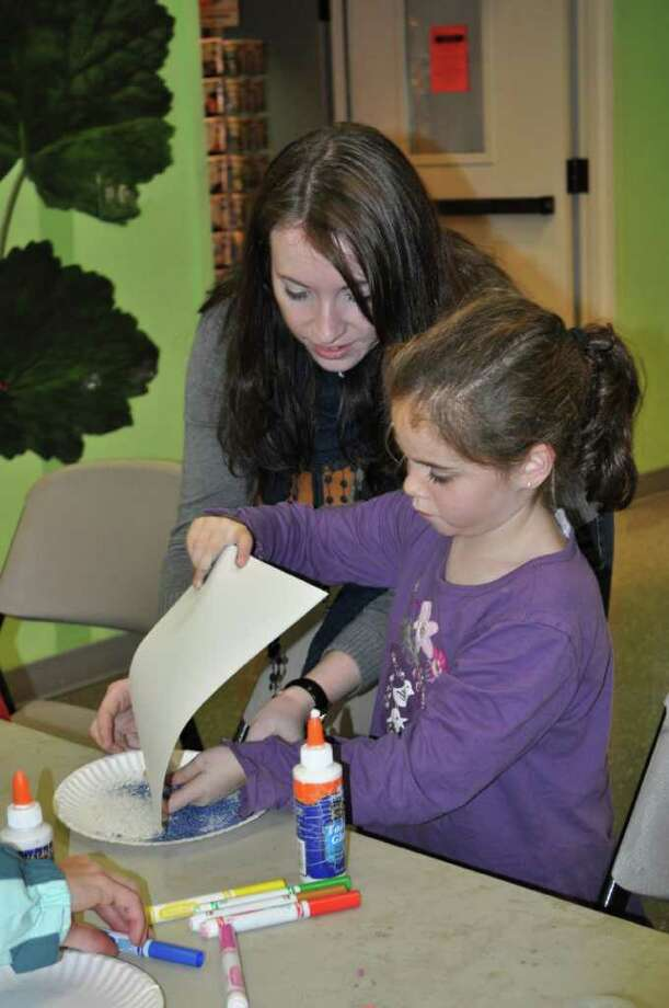 """Bruce Museum volunteer Julie Barry helps Elizabeth Fink at a recent Bruce Museum workshop. The Bruce Museum presents """"Vacation Workshops: Paper Theaters,"""" from Dec. 28-30. Photo: Contributed Photo / Connecticut Post Contributed"""