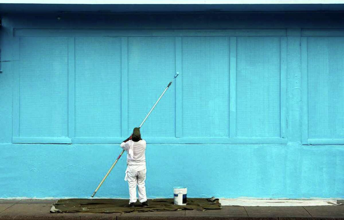 METRO: Omar Gonalez paints the Cesar Chavez building of the Guadalupe Cultural Arts Center, on Tuesday Sept. 14, 2010. The building was being prepped for a mural. HELEN L. MONTOYA/hmontoya@express-news.net