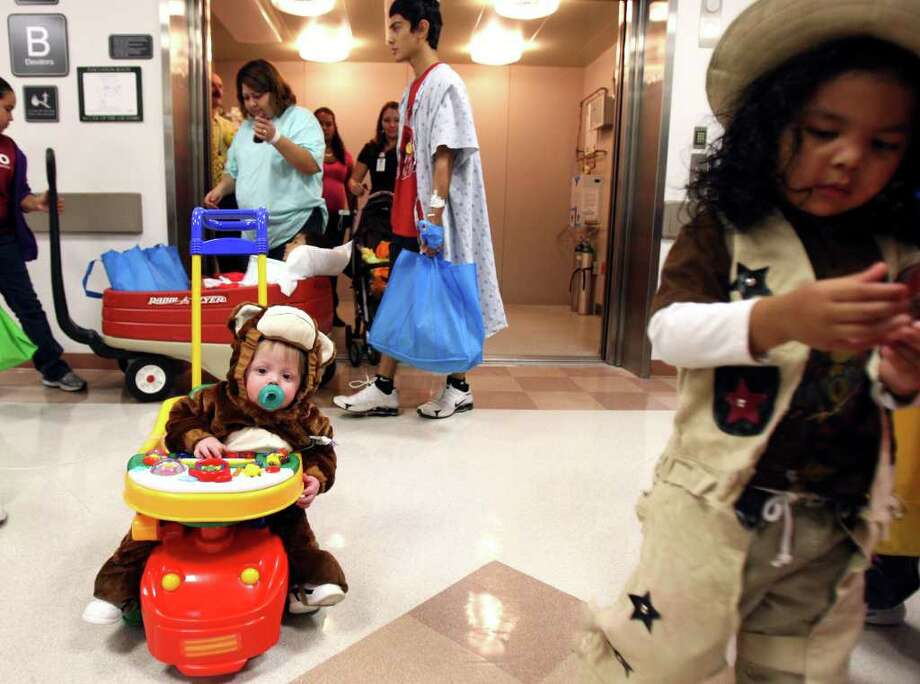 METRO:  Anthony Valenzuela, 13 months (left) wears a monkey costume as he trick-or-treats through University Hospital along with other current and formerJaney Briscoe Children's Center pediatric patients on Friday Oct. 29, 2010.  HELEN L. MONTOYA/hmontoya@express-news.net Photo: HELEN L. MONTOYA, SAN ANTONIO EXPRESS-NEWS / hmontoya@express-news.net