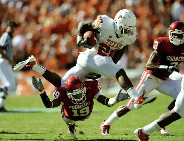 Texas running back Fozzy Whittaker jumps over Oklahoma defender Demontre Hurst during the first-half of the annual Red River Rivalry at the Cotton Bowl in Dallas on Saturday, Oct. 2, 2010. Photo: BILLY CALZADA, SAN ANTONIO EXPRESS-NEWS / gcalzada@express-news.net