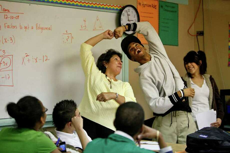 "Sam Houston math teacher Lorraine Dominguez, left, does a fist bump  with junior Javoi Lawson, 17, during algebra class on Thursday, December, 10, 2009. ""She tries to encourage us to work harder but she keeps it fun and she maintains a high energy in the classroom. She tries to keep everybody up instead of being down and making everything just hard,"" Lawson says of Dominguez who is known for singing ""Found a Peanut"" to explain the box method for factoring a polynomial. Many of her colleagues credit her with the improved math scores at the school.  LISA KRANTZ/lkrantz@express-news Photo: LISA KRANTZ, SAN ANTONIO EXPRESS-NEWS / SAN ANTONIO EXPRESS-NEWS"